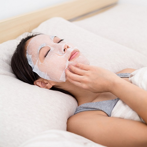 Asian Young Woman having paper mask on bed